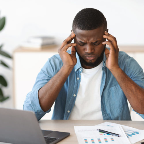 Headache Concept. Stressed Black Man Suffering From Migraine At Workplace, Tired African American Guy Sitting At Desk With Laptop And Touching Temples, Having Strong Pain Or Blood Pressure, Free Space